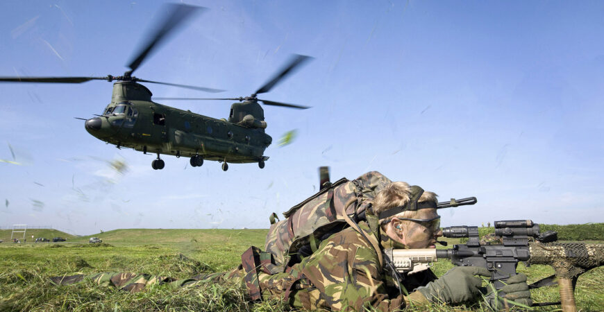landmachtmilitair-ligt-tussen-opwaaiend-gras-door-opstijgende-chinook-transporthelikopter